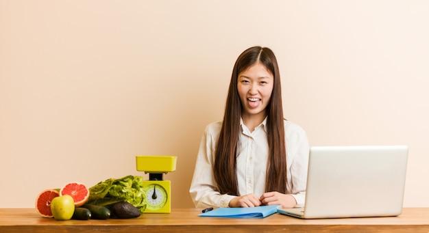 Jonge voedingsdeskundige chinese vrouw die met haar laptop werkt grappig en vriendschappelijk steekt hem tong.
