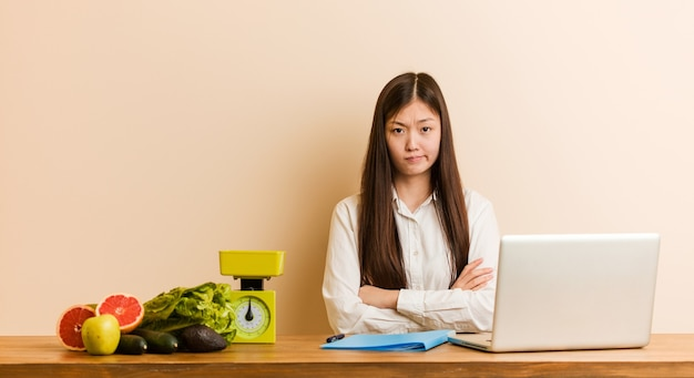 Jonge voedingsdeskundige chinese vrouw die met haar laptop werkt ongelukkig in de camera kijken met sarcastische uitdrukking.