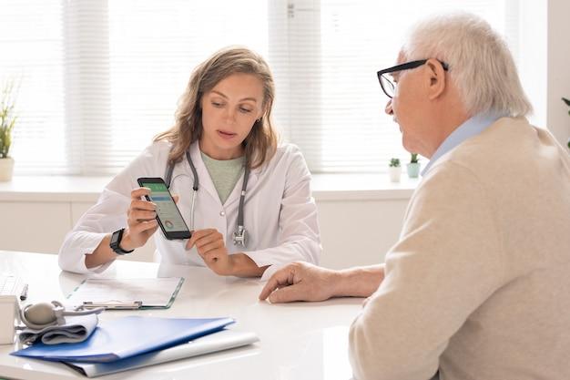 Jonge voedingsdeskundige geeft aanbevelingen over voeding en trainingen aan senior patiënt terwijl hij gegevens op smartphonescherm toont