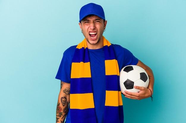 Jonge voetbal fan man met een bal geïsoleerd op blauwe achtergrond schreeuwen erg boos en agressief.