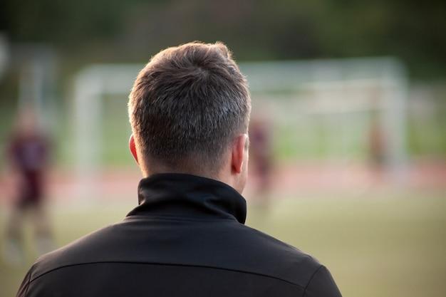 Jonge voetbalcoach let op het team tijdens de wedstrijd