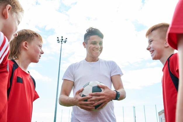 Jonge voetbalcoach praten met kinderen