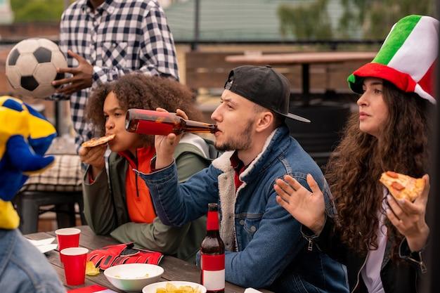 Jonge voetbalfans bier drinken en pizza eten terwijl ze kijken naar het spel van hun team op het terras