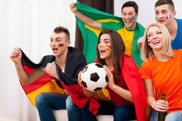 Jonge voetbalfans tijdens het kijken naar wedstrijd op tv