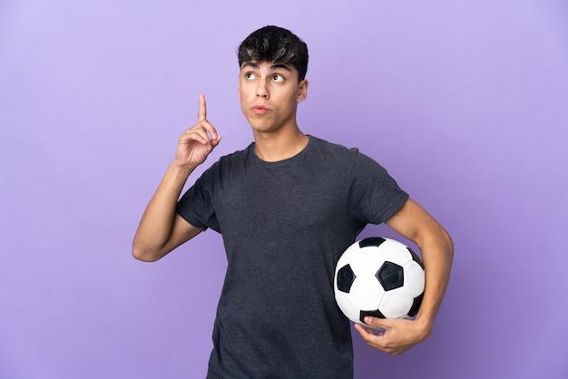 Jonge voetballer man over paars denken een idee met de vinger omhoog