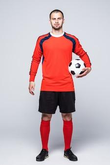 Jonge voetballer met bal onder hand gekleed in rode trui voor wit