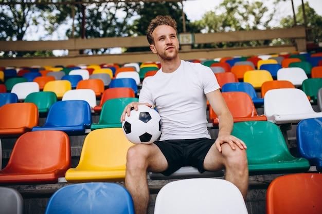 Jonge voetballer op tribunes kijken naar het spel