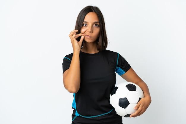 Jonge voetballer vrouw geïsoleerd op een witte achtergrond met een teken van stilte gebaar