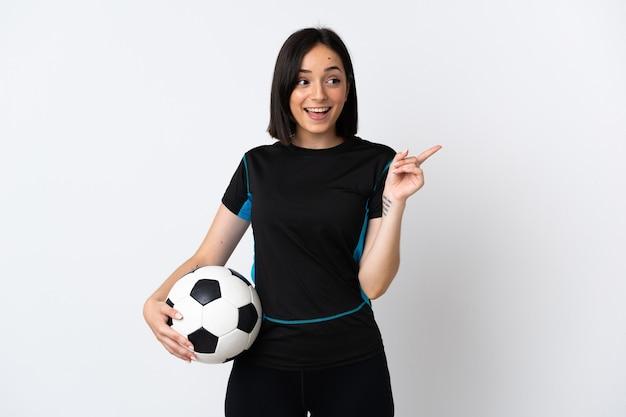 Jonge voetballer vrouw geïsoleerd op een witte muur van plan om de oplossing te realiseren terwijl het opheffen van een vinger