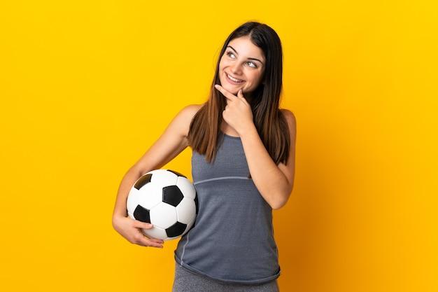 Jonge voetballer vrouw geïsoleerd op geel te kijken tijdens het glimlachen