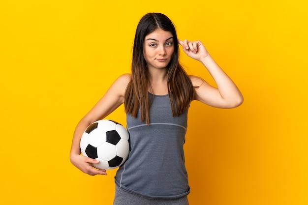 Jonge voetballer vrouw geïsoleerd op geel twijfels en denken