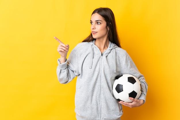 Jonge voetballer vrouw geïsoleerd op gele achtergrond van plan om de oplossing te realiseren terwijl het opheffen van een vinger