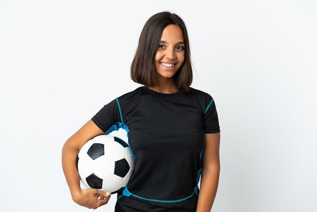 Jonge voetballer vrouw geïsoleerd op wit te kijken tijdens het glimlachen