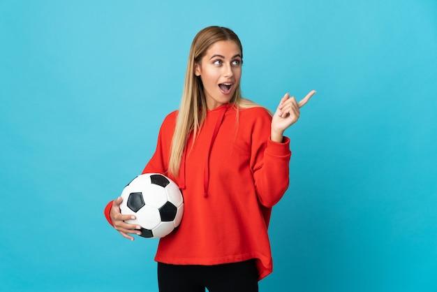 Jonge voetballer vrouw op blauw van plan om de oplossing te realiseren terwijl ze een vinger opheft