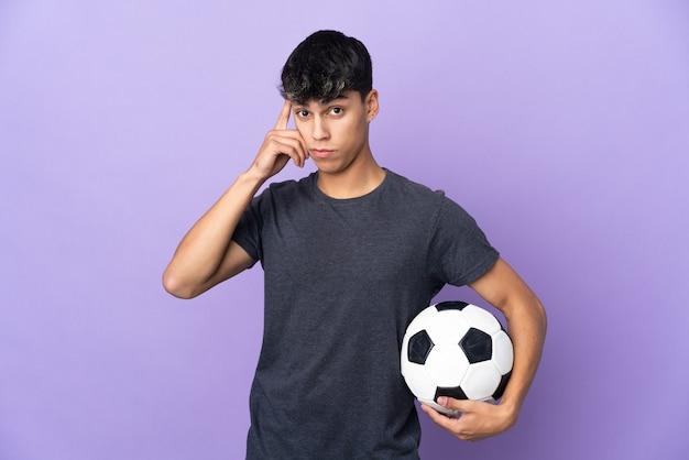 Jonge voetballermens over geïsoleerde purpere muur die een idee denken