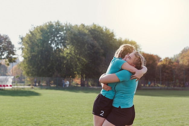 Jonge voetballers omhelzen elkaar