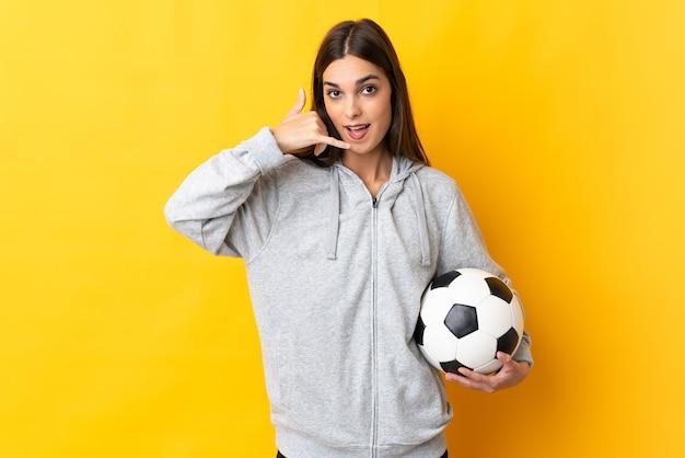 Jonge voetballervrouw die op geel telefoongebaar maakt.