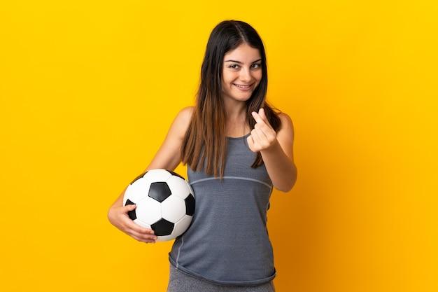 Jonge voetballervrouw die op geel wordt geïsoleerd die geldgebaar maakt