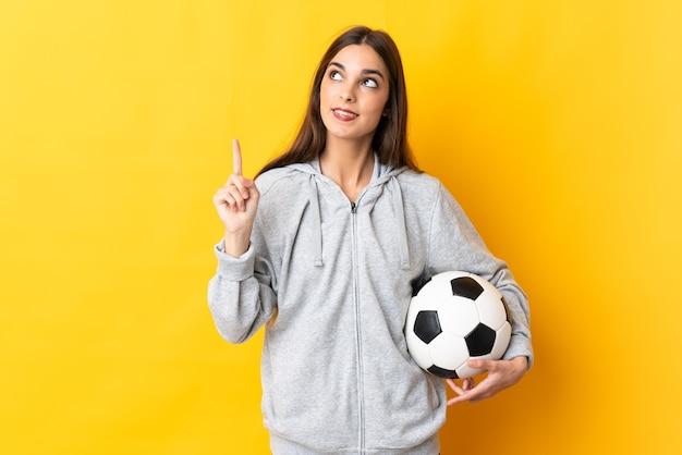 Jonge voetballervrouw die op gele achtergrond wordt geïsoleerd die een geweldig idee benadrukt