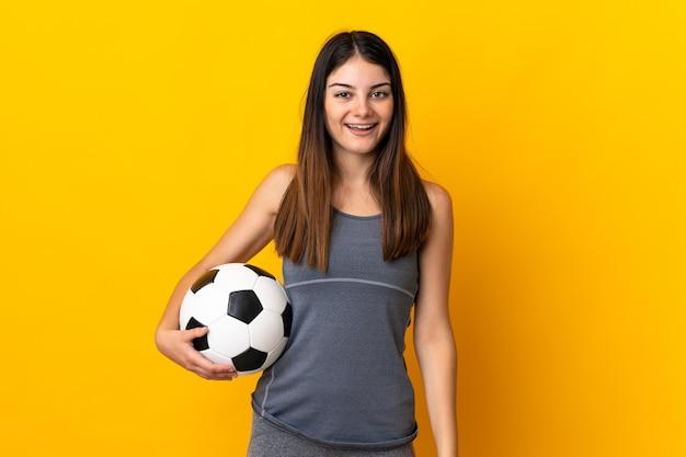 Jonge voetballervrouw die op gele muur met verrassingsgelaatsuitdrukking wordt geïsoleerd