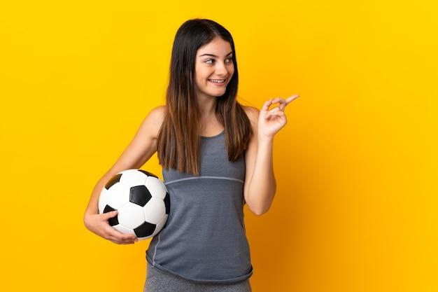Jonge voetballervrouw die op gele muur wordt geïsoleerd die van plan is de oplossing te realiseren terwijl het opheffen van een vinger