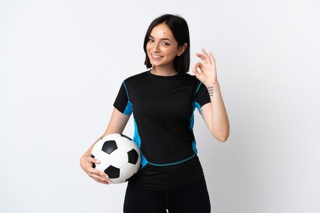 Jonge voetballervrouw die op wit wordt geïsoleerd dat ok teken met vingers toont