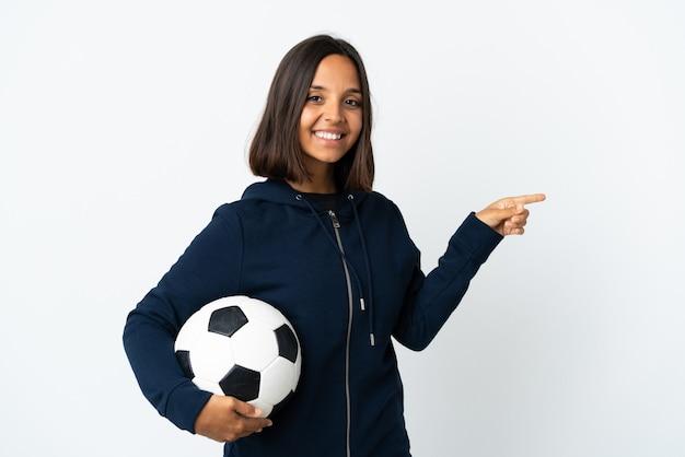 Jonge voetballervrouw die op witte muur wordt geïsoleerd die vinger aan de kant richt