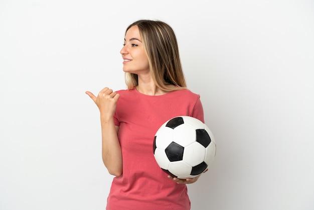 Jonge voetballervrouw over geïsoleerde witte muur die naar de zijkant wijst om een product te presenteren