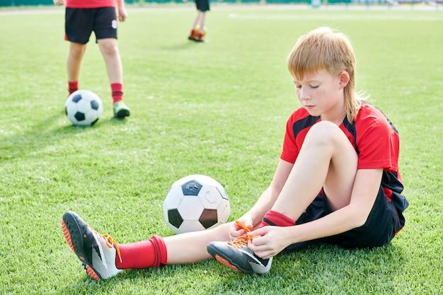 Jonge voetbalster die zijn schoenen bindt