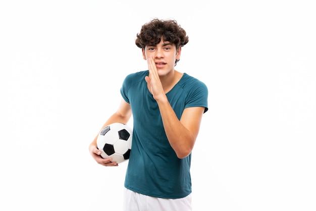 Jonge voetbalstermens over geïsoleerde witte muur die iets fluisteren