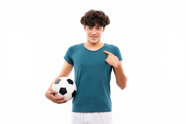 Jonge voetbalstermens over geïsoleerde witte muur met verrassingsgelaatsuitdrukking
