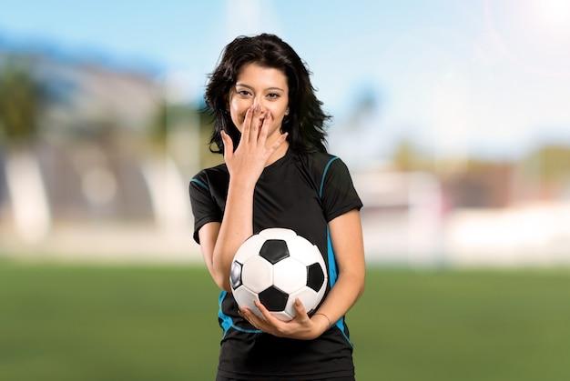Jonge voetbalstervrouw met verrassingsgelaatsuitdrukking bij in openlucht