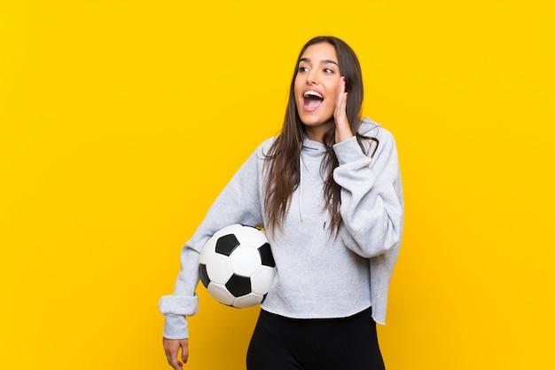 Jonge voetbalstervrouw over geïsoleerde gele muur die met wijd open mond schreeuwen