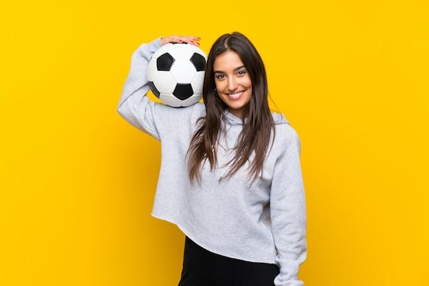 Jonge voetbalstervrouw over geïsoleerde gele muur