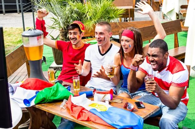 Jonge voetbalsupporters juichen met bier kijken naar voetbalwedstrijd