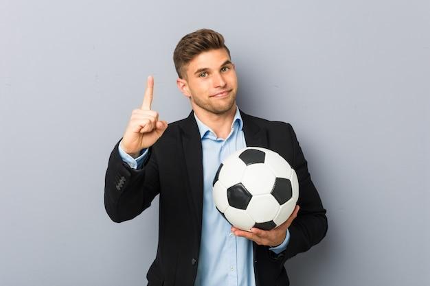 Jonge voetbaltrainer die nummer één met vinger toont.