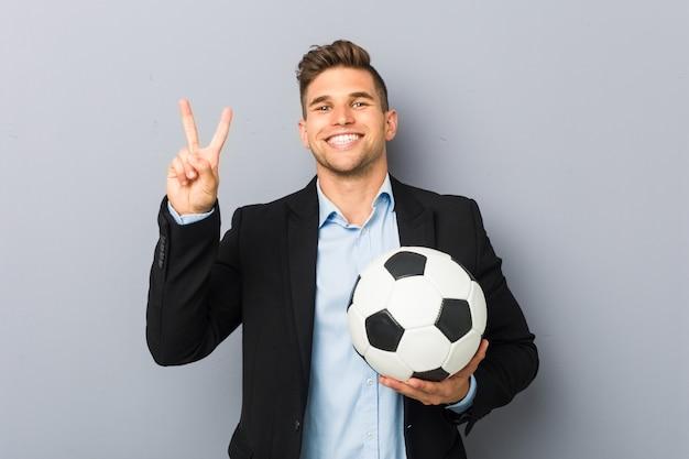 Jonge voetbaltrainer die nummer twee met vingers toont.