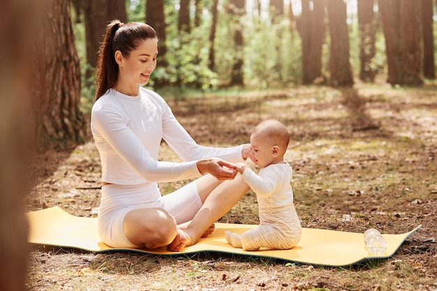 Jonge volwassen aantrekkelijke moeder zittend op karemat met gekruiste benen, hand in hand haar kleine baby kind, tijd samen doorbrengen in bos, gezonde levensstijl.