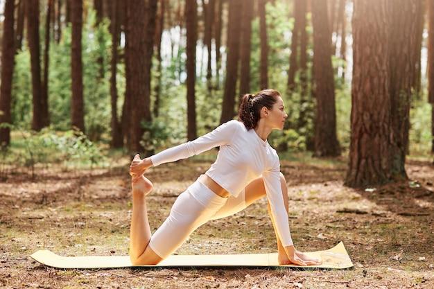 Jonge volwassen aantrekkelijke vrouw in witte sportkleding die yoga beoefent op karemat op open lucht in groen bos, training, sportieve vrouw die geniet van training op de natuur.