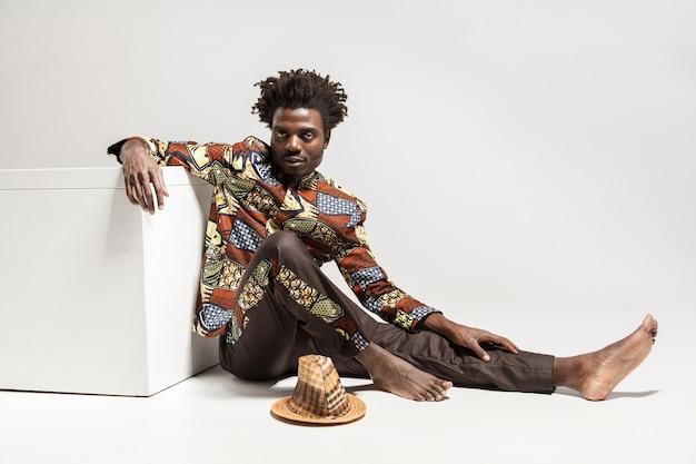 Jonge volwassen afrikaanse man zittend op de vloer in de buurt van kubus