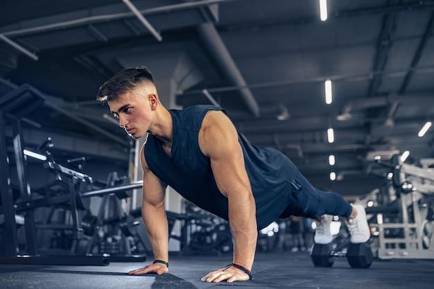Jonge volwassen atleet doet push-ups als onderdeel van bodybuilding-training