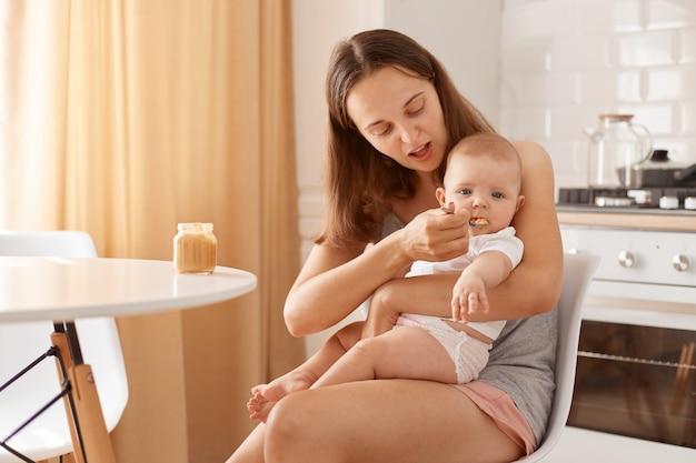 Jonge volwassen blanke, donkerharige moeder die haar dochtertje voedt met fruit- of groentepuree, zittend aan tafel in de keuken, vrouw met een casual mouwloos t-shirt en een korte broek.