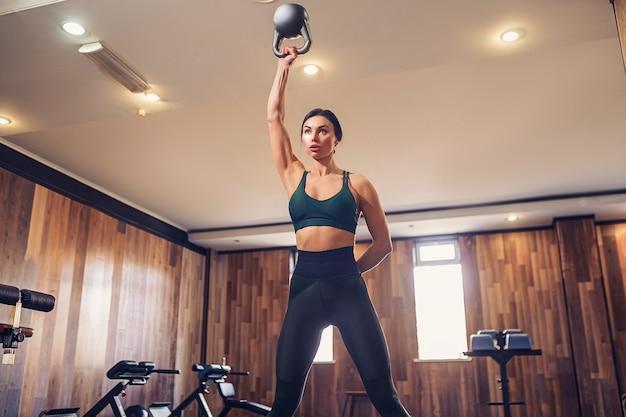 Jonge volwassen fitnessvrouw die schommelingsoefening met een kettlebell doet als onderdeel van een fitnesstraining