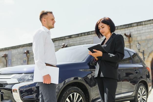 Jonge volwassen glimlachende man en vrouw in zakelijke donkere pakken die zich dichtbij een auto bevinden die een tablet gebruiken