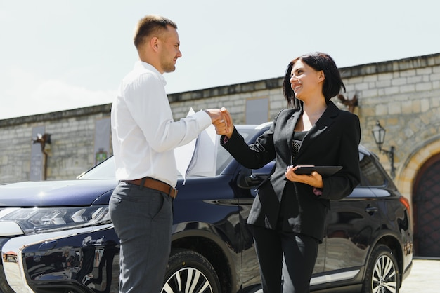 Jonge volwassen glimlachende man en vrouw in zakelijke donkere pakken die zich dichtbij een auto bevinden die handen schudden