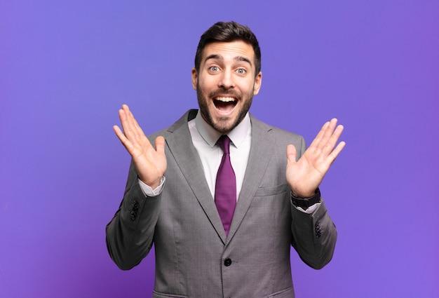 Jonge volwassen knappe zakenman die er blij en opgewonden uitziet, geschokt door een onverwachte verrassing met beide handen open naast het gezicht