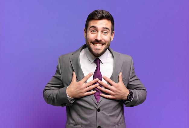 Jonge volwassen knappe zakenman die er blij, verrast, trots en opgewonden uitziet, wijzend naar zichzelf
