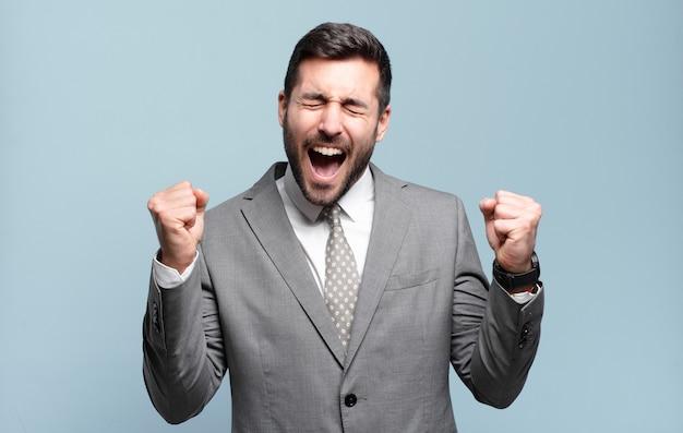 Jonge volwassen knappe zakenman die er buitengewoon blij en verrast uitziet