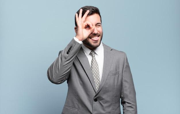 Jonge volwassen knappe zakenman die gelukkig lacht met een grappig gezicht, een grapje maakt en door een kijkgaatje kijkt, geheimen bespioneert
