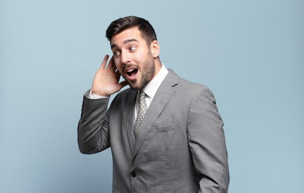 Jonge volwassen knappe zakenman die lacht, nieuwsgierig naar de zijkant kijkt, probeert te roddelen of een geheim afluistert